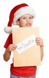 Begrepp för jul för vinterferie - pojke i hatt med bokstaven till santa på isolerad vit Royaltyfri Fotografi