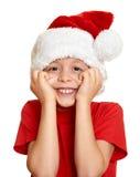 Begrepp för jul för vinterferie - pojke i santa hattstående på isolerad vit Arkivfoto