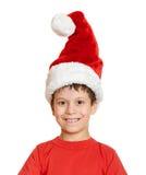 Begrepp för jul för vinterferie - pojke i santa hattstående på isolerad vit Arkivbild