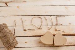 Begrepp för kärlekshistorier och för valentin dag Raden, inskrifterna från den och handgjorda papphjärtor på ett naturligt arkivfoto