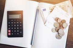 Begrepp för kontobok med kassaräkningar och mynt, anteckningsbok och räknemaskin royaltyfri foto