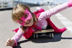 Begrepp för liten flickaridningskateboard arkivfoton