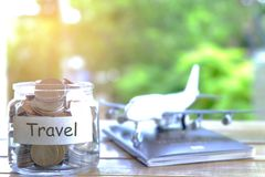 Begrepp för loppbudget Begrepp för lopppengarbesparingar Samla pengar i moneybox för lopp Pengarkrus med mynt, flygplan, och royaltyfri foto