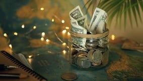 Begrepp för loppbudget Pengar sparade för semester i den glass kruset på världskartabakgrund arkivfilmer