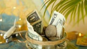 Begrepp för loppbudget Pengar sparade för semester i den glass kruset på världskartabakgrund lager videofilmer