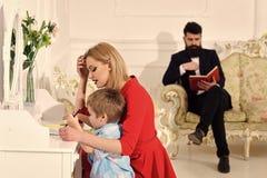 Begrepp för lycka för barnbarndombarn Begrepp för hem- skolgång Faderläsebok, medan modern undervisar sonen arkivfoton