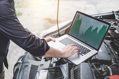 Begrepp för maskin för servicebilmotor, repairman för bilmekaniker som kontrollerar en bilmotor med att använda datordiagnostikst fotografering för bildbyråer