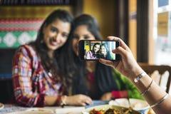 Begrepp för mobiltelefon för kommunikation för kvinnakamratskapsamhörighetskänsla royaltyfri fotografi