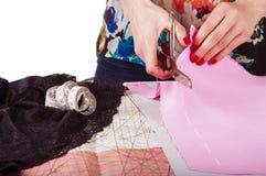 Begrepp för modeformgivare Kvinnas händer som klipper rosa tyg i st Arkivbild