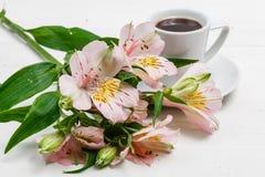 Begrepp för morgonkaffekopp Rosa blommabukett på tappningbakgrund arkivbild