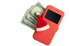 Begrepp för nytt år av det finansiella gömstället på en mobiltelefon Smartphone i ett röda fall, Santa Claus hatt och trehundra o arkivbilder