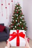 Begrepp för nytt år - gåvaask i den manliga handen över julbackgrou Arkivfoto