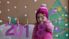 Begrepp 2018 för nytt år Härlig liten flicka som dekorerar talet för nytt år bakgrund av en målad julgran och