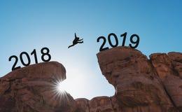 Begrepp för nytt år, kontur en man som hoppar över klippan från 2018 till 2019 royaltyfri foto