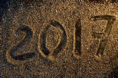 Begrepp för nytt år 2017 Nummer 2017 på den guld- sandtexturen Royaltyfri Bild