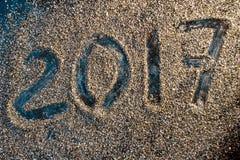 Begrepp för nytt år 2017 Nummer 2017 på den guld- sandtexturen Royaltyfria Bilder
