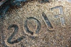 Begrepp för nytt år 2017 Nummer 2017 på den guld- sandtexturen Arkivbilder