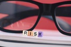 Begrepp för riskledning Riskordkub på boken över röd backgrou fotografering för bildbyråer