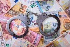 Begrepp för smutsiga pengar och korruption- handbojor med euroräkningar arkivfoto