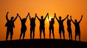 Begrepp för solnedgång för grupp människorberöm gladlynt arkivfoto