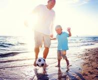 Begrepp för sommar för faderSon Playing Soccer strand royaltyfri foto
