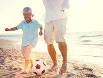 Begrepp för sommar för faderSon Playing Soccer strand fotografering för bildbyråer
