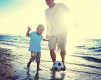 Begrepp för sommar för faderSon Playing Soccer strand Arkivbilder