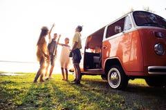 Begrepp för sommarferier, för vägtur, semester-, lopp- och folk- le unga hippievänner som har gyckel över minivan royaltyfria bilder