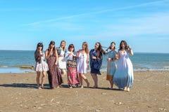 Begrepp för sommarsemester, ferie-, lopp- och folk- grupp av att le unga kvinnor på stranden arkivfoto
