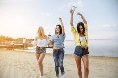 Begrepp för sommarsemester, ferie-, lopp- och folk- grupp av att le unga kvinnor som dansar på stranden royaltyfria bilder