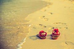 Begrepp för sommarsemester--Flipflops på en sandig strand Arkivfoto
