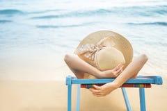 Begrepp för sommarstrandsemester, Asien kvinna med hatten som kopplar av, och arm upp på stolstranden på Koh Mak som är trad, Tha arkivfoton
