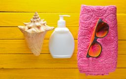 Begrepp för strandsemesterort Den kvinnliga strandtillbehören på slösar gul träbakgrund Shell exponeringsglas, handduk, sunblock Royaltyfri Foto