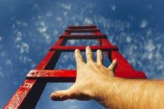 Begrepp för tillväxt för utvecklingsmotivationkarriär Mans handen som når för den röda stegen som leder till en blå himmel arkivfoton