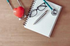 Begrepp för vård- undersökning, skrivbords- workspace för doktors` s med stethosc arkivbild