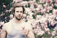 Begrepp för vårsäsong Ny liv och optimism Macho med skägget i grå singlet på blom- bakgrund royaltyfri foto