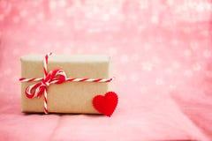 Begrepp för valentingåvaask med röd hjärta på sött rosa tyg b Arkivbild
