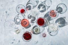Begrepp för vinavsmakning - exponeringsglas med olikt vin på marmorbakgrund royaltyfria bilder