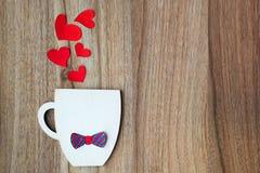 Begrepp f?r faderdag Dekorativ kopp med pappersflugan och röda hjärtor på träbakgrund Copyspace royaltyfria foton