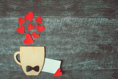 Begrepp f?r faderdag red steg F?delsedag Dekorativ kopp med flugan och hj?rtor p? tr?bakgrund Copyspace tomt kort royaltyfria bilder