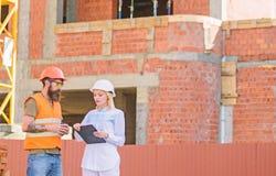 Begrepp f?r konstruktionslagkommunikation Diskutera framstegplanet Den kvinnateknikern och byggm?staren meddelar konstruktionspla arkivfoto