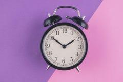 Begrepp f?r Tid ledning, ringklocka p? purpurf?rgad bakgrund fotografering för bildbyråer
