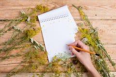 Begrepp för alternativ medicin - handen skriver på ett recept i notepad Royaltyfri Bild