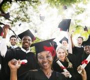 Begrepp för beröm för framgång för mångfaldstudentavläggande av examen Arkivfoton