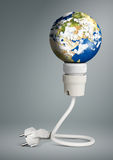 Begrepp för ren energi, ljus kula med planetjord och propp Royaltyfri Fotografi