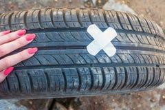 Begrepp: gummihjulreparation Kvinnan gjorde lappen på hjulet av en bil av bactericidal självhäftande murbruk royaltyfri bild