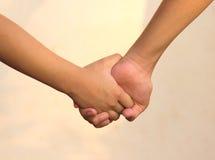Begrepp hand - in - hand som tillsammans rymmer händer Arkivfoto
