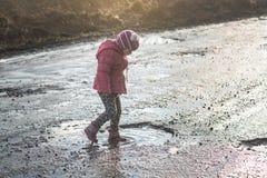 Begrepp - lycklig barndom Lilla flickan spelar i pöl, gyckel för barn` s, smutsar ner och blöter skor, liv i byn, solljus arkivfoto