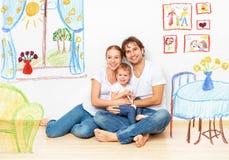 Begrepp: lycklig ung familj i nytt lägenhetdröm och plan in Royaltyfri Bild