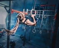 Begrepp: makt styrka, sund livsstil, sport Kraftig attraktiv muskulös kvinna på den CrossFit idrottshallen arkivbilder